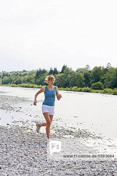 Mid adult woman jogging at Isar river