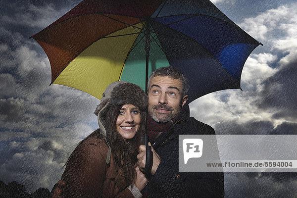 Deutschland  Köln  Paar mit Regenschirm  lächelnd