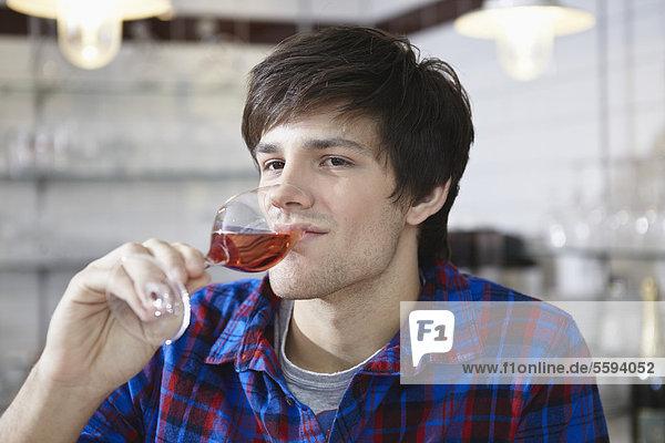 Junger Mann trinkt Wein  lächelnd