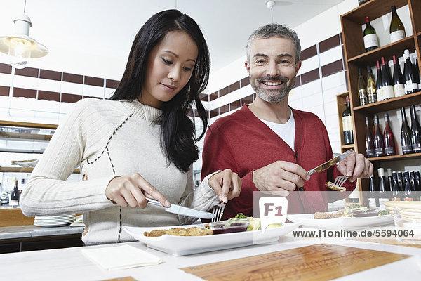 Deutschland  Köln  Paar Essen in der Küche  lächelnd