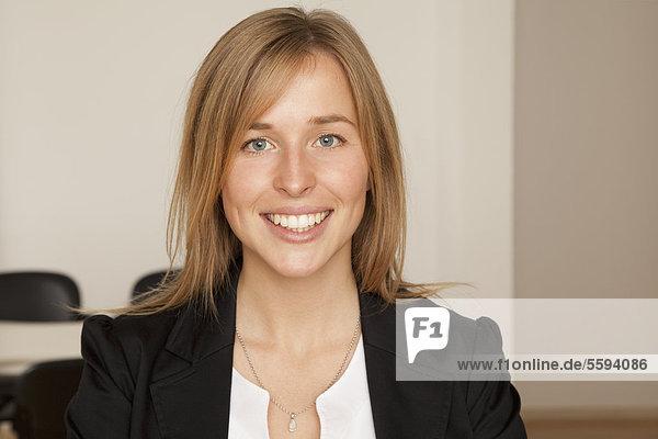 Junge Frau im Büro  lächelnd  Portrait