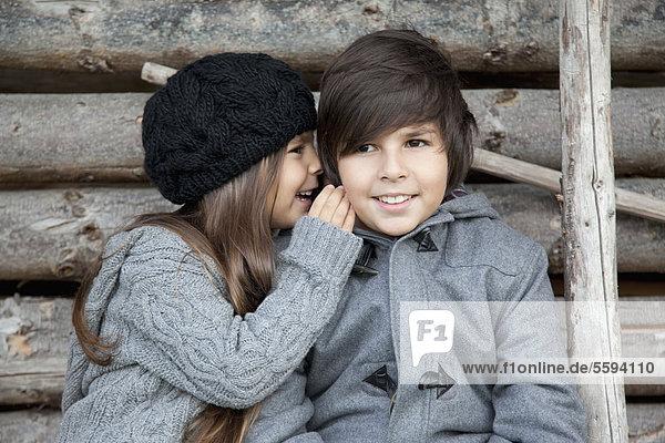 Junge und Mädchen flüstern sich zu.