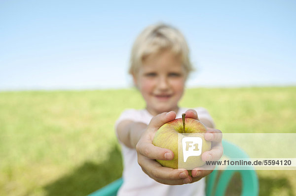 Girl holding apple fruit in grass meadow  smiling  portrait
