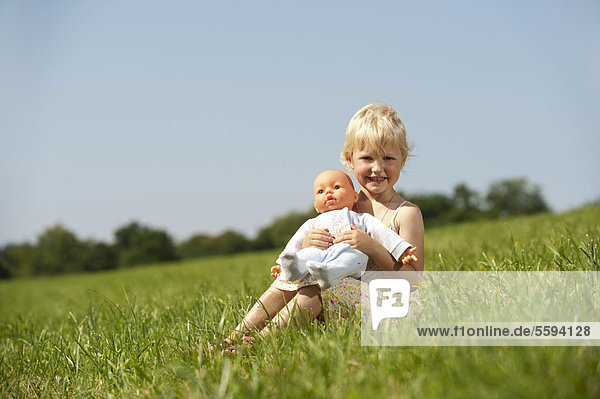Girl with baby doll in grass  smiling  portrait