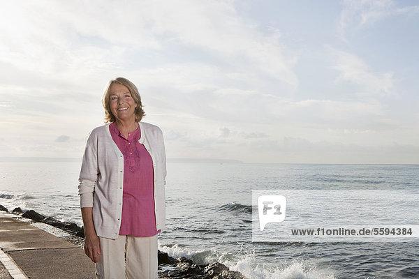Spanien  Mallorca  Seniorin am Meer stehend  lächelnd  Portrait