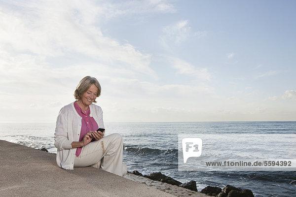 Spanien  Mallorca  Seniorin sitzend und telefonierend am Meer  lächelnd