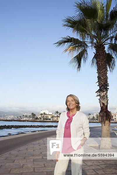 Spanien  Mallorca  Seniorin am Meer stehend  lächelnd