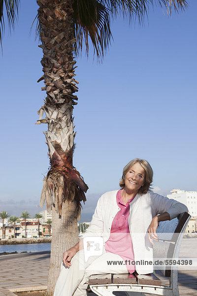 Spanien  Mallorca  Seniorin auf Bank am Meer sitzend  lächelnd