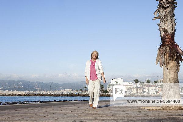 Spanien  Mallorca  Seniorenfrau am Meer entlang  lächelnd