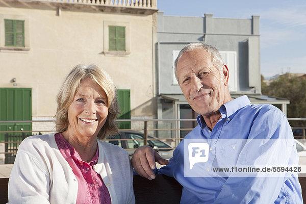 Spanien  Mallorca  Seniorenpaar auf Bank sitzend  lächelnd  Portrait