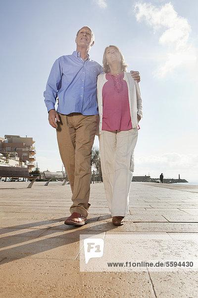 Spanien  Mallorca  Seniorenpaar  zusammen gehen  lächelnd