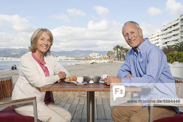 Spanien  Mallorca  Seniorenpaar im Restaurant am Strand  lächelnd  Portrait