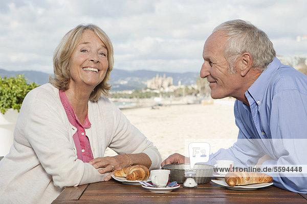 Spanien  Mallorca  Seniorenpaar im Restaurant am Strand  lächelnd