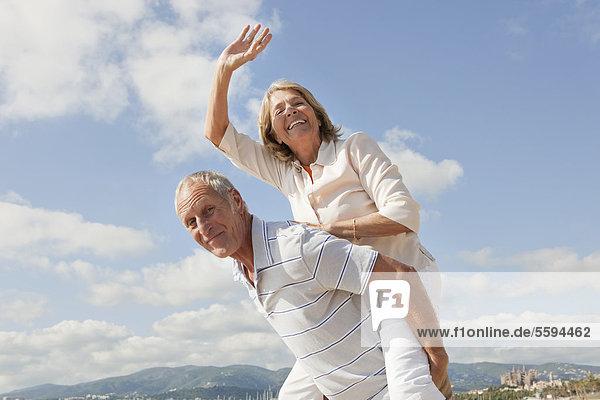 Spanien  Mallorca  Senior Mann  der die Frau am Strand huckepack reitet.
