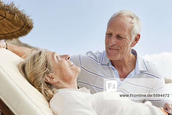 Spanien  Mallorca  Senior Mann sieht Frau auf Liegestuhl am Strand ruhen