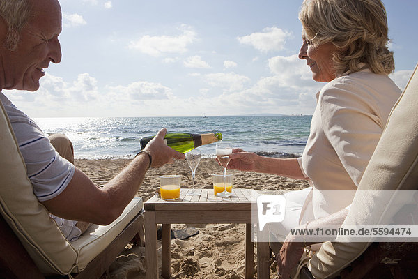 Spanien  Mallorca  Seniorenpaar beim Sekttrinken am Strand