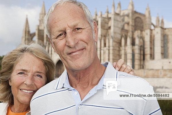 Spanien  Mallorca  Palma  Seniorenpaar lächelnd mit Kathedrale Santa Maria  Portrait