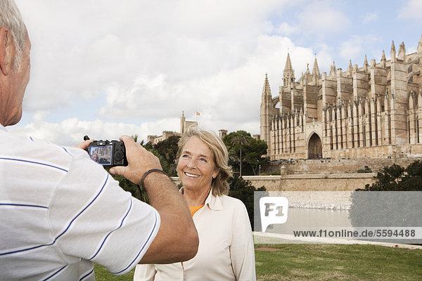 Spanien  Mallorca  Palma  Seniorenpaar lächelnd beim Fotografieren mit der Kathedrale Santa Maria