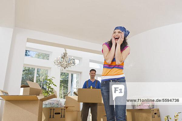 Frau lacht mit Mann im Hintergrund  lächelnd