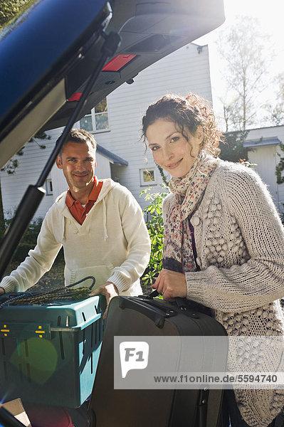 Deutschland  Bayern  Grobenzell  Paar Ladesack ins Auto  lächelnd