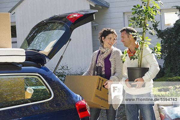 Deutschland  Bayern  Grobenzell  Paar Ladeboxen ins Auto  lächelnd