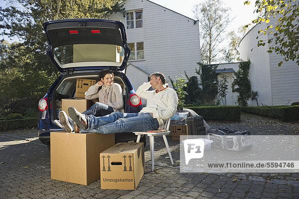 Deutschland  Bayern  Grobenzell  Paar entspannt auf Stuhl neben dem Auto  lächelnd