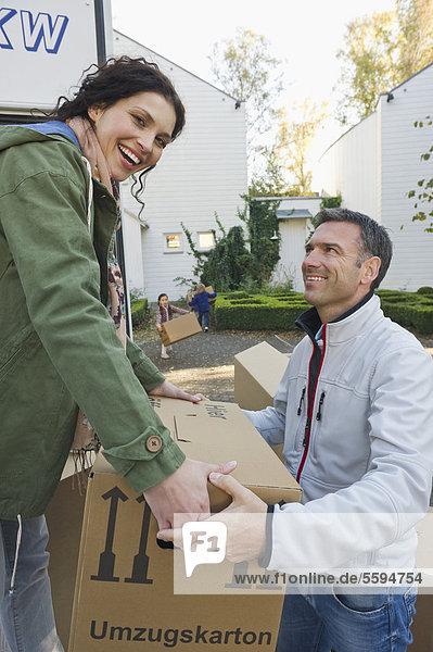 Deutschland  Bayern  Grobenzell  Paar Ladekisten in LKW  lächelnd
