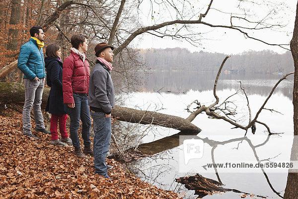 Männer und Frauen  die am See stehen und den Blick auf den See richten.