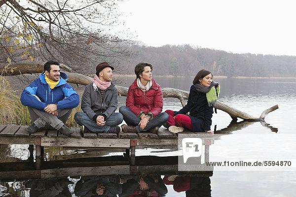Männer und Frauen sitzen auf dem Pier