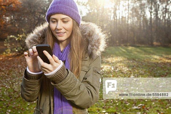 Mittlere erwachsene Frau mit Handy