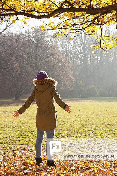 Mittlere erwachsene Frau im Sonnenlicht stehend