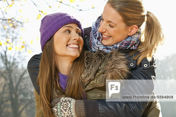 Woman giving piggy back ride to her friend  smiling