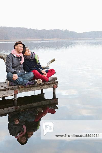 Deutschland  Berlin  Wandlitz  Paar am Pier sitzend  lächelnd