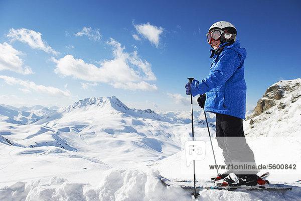 Junge in Skiern auf verschneiter Bergspitze