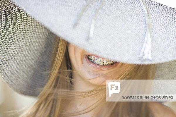 Lächelndes Mädchen in Hosenträgern mit Sonnenhut
