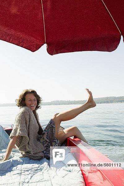 Woman relaxing in boat on still lake