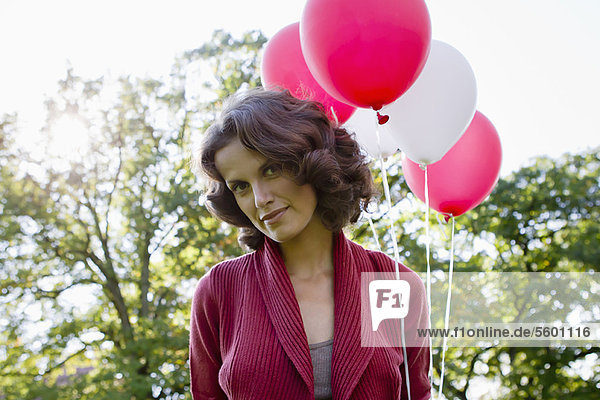 Woman carrying balloons outdoors