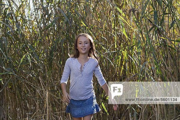 Smiling girl walking in wheatfield