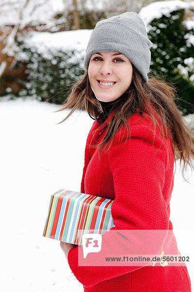 Frau mit verpacktem Geschenk im Schnee