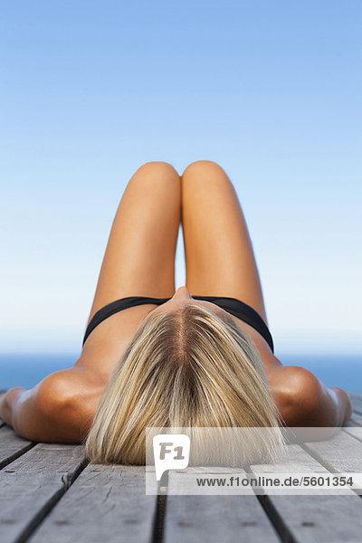 Frau beim Sonnenbaden auf dem hölzernen Pier