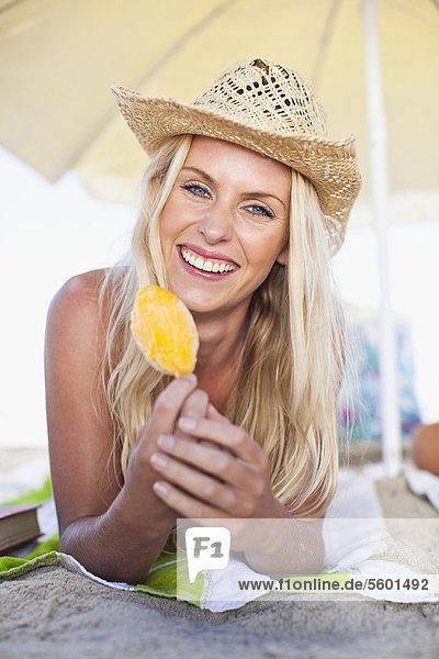Eis am Stiel  Stieleis  Frau  lächeln  Strand  essen  essend  isst