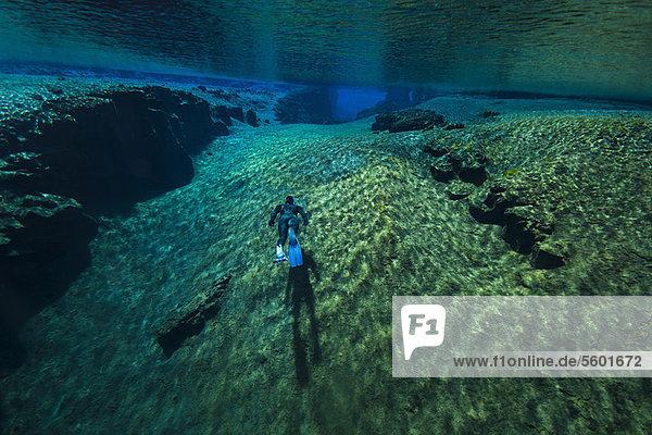 Taucher beim Schwimmen in Felsformationen