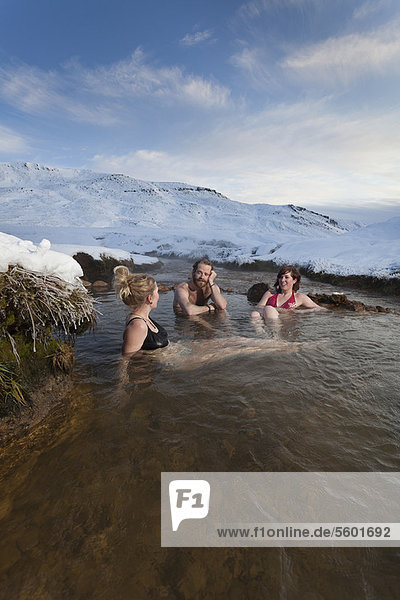 Friends relaxing in glacial hot spring