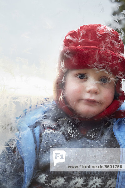 Boy looking in frosty window