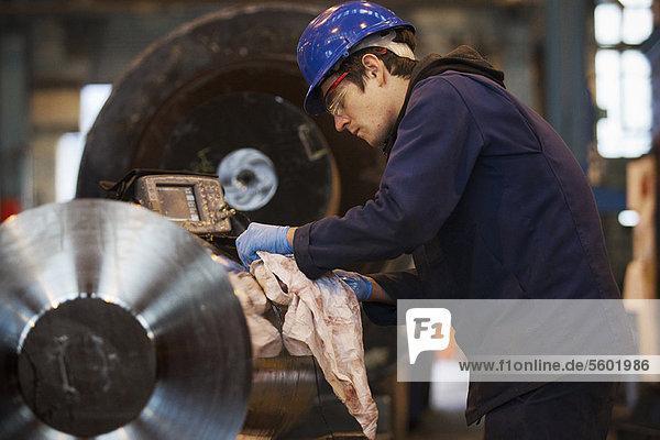 Worker cleaning metal in steel forge