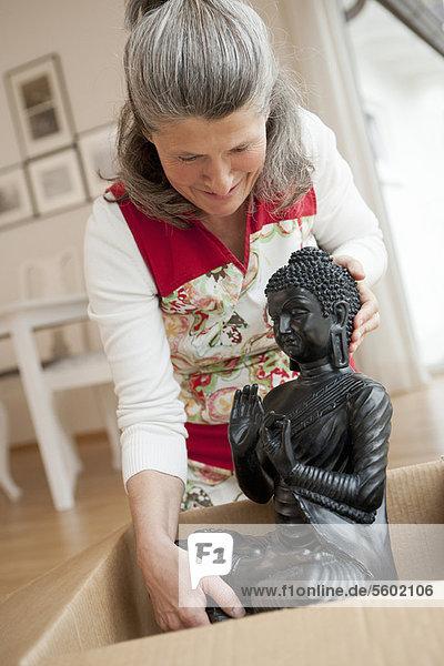 Ältere Frau beim Auspacken der Buddha-Statue