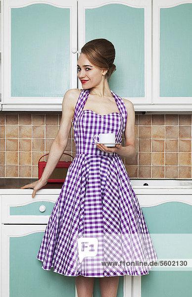 Frau bei einer Tasse Kaffee in der Küche