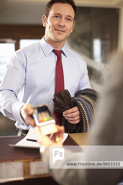 Schreibtisch Geschäftsmann Hotel frontal bezahlen zahlen