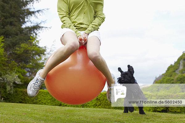 Frau auf Hüpfburg spielt mit Hund