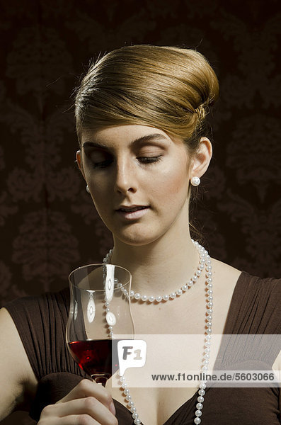 Young woman wearing a pearl necklace and pearl earrings  beside red wine in a wine glass
